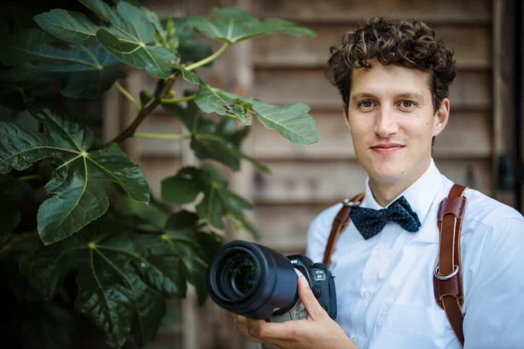 Jongeman met een camera en krullen op een bruiloft.